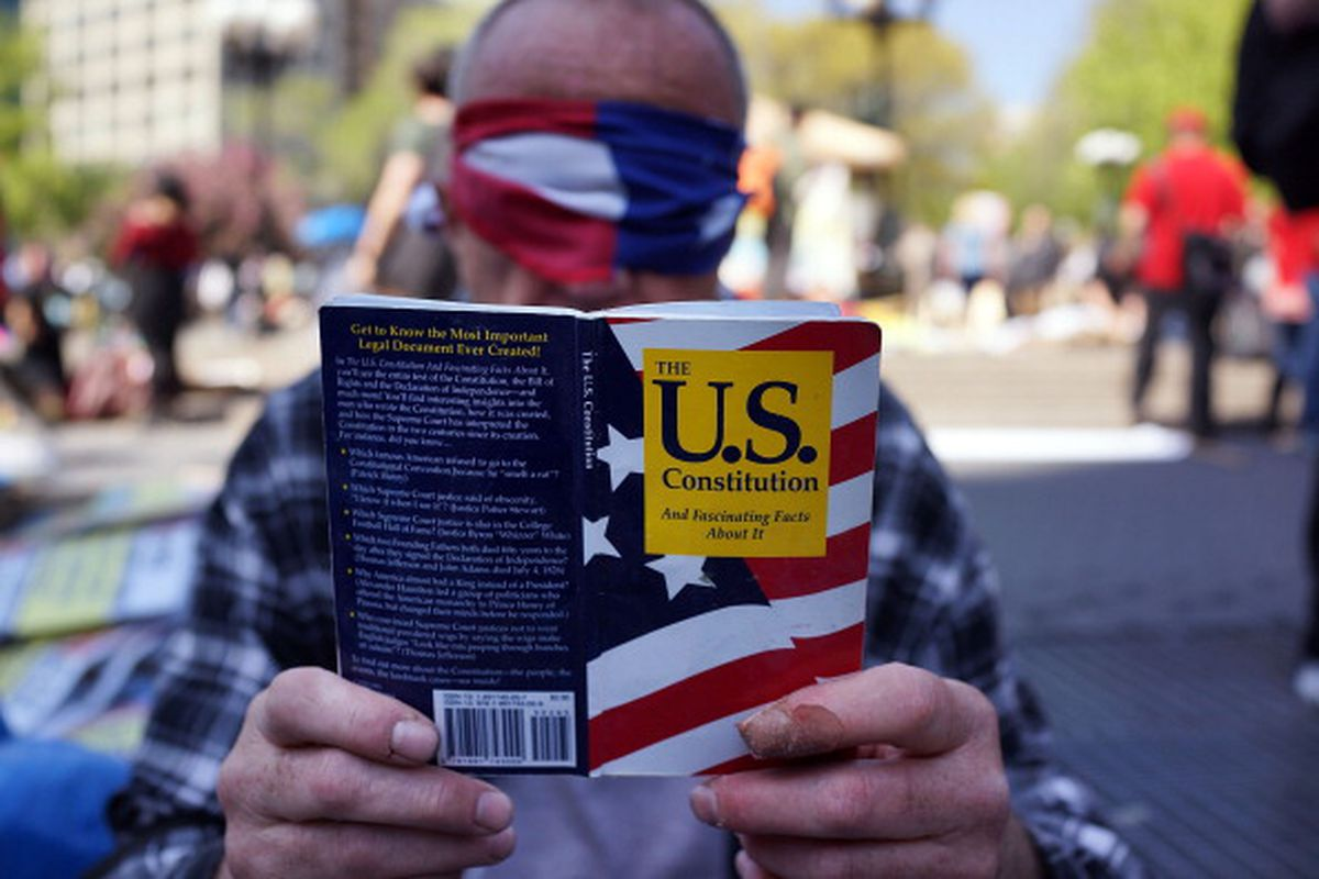 A man with an American Flag tied around his eyes and holding a copy of the U.S. Constitution sits with demonstrators preparing to march down Broadway on International Workers Day, or Labor Day, on May 1, 2014 in New York City.