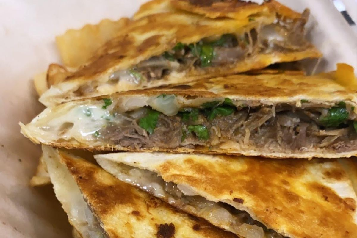 A pile of golden brown fried Nihari Birria shredded lamb meat-stuffed quesadillas with jalapenos and ginger