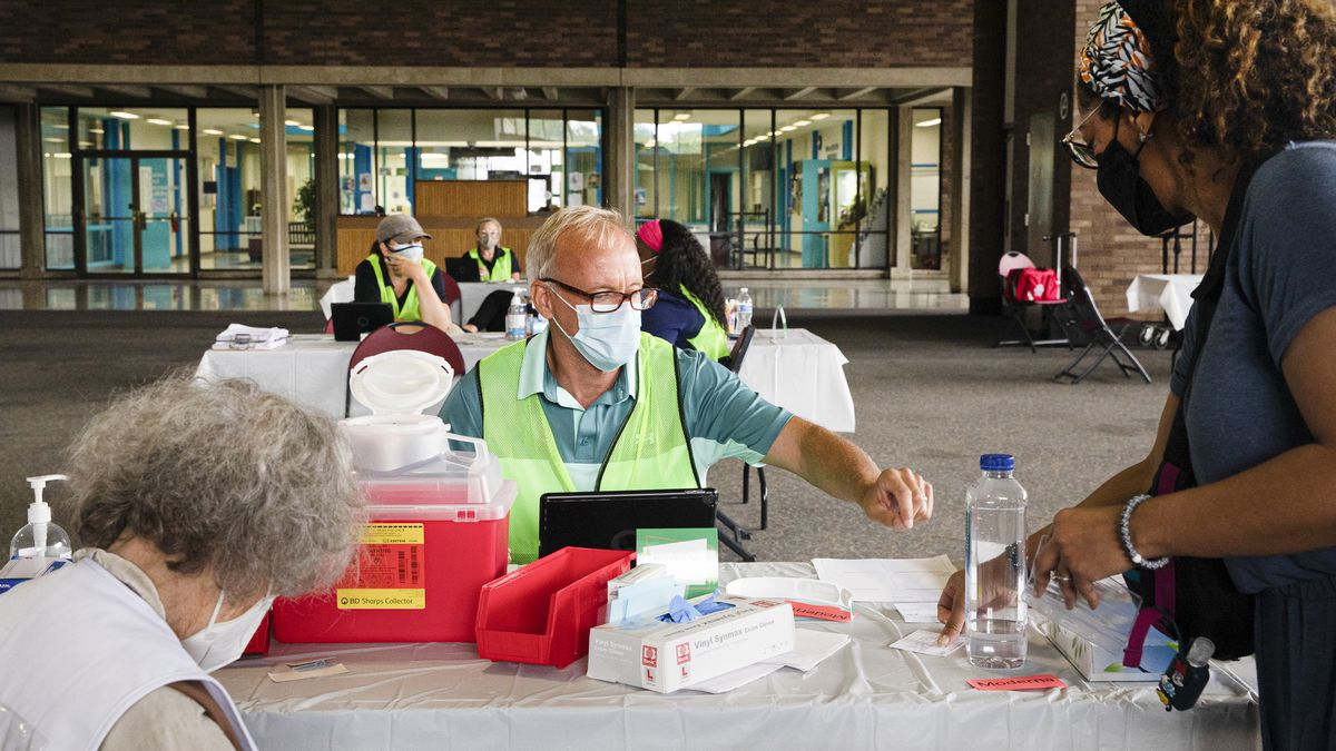 A patient shows their vaccination card to a person sitting at an outdoor table distributing vaccine shots.