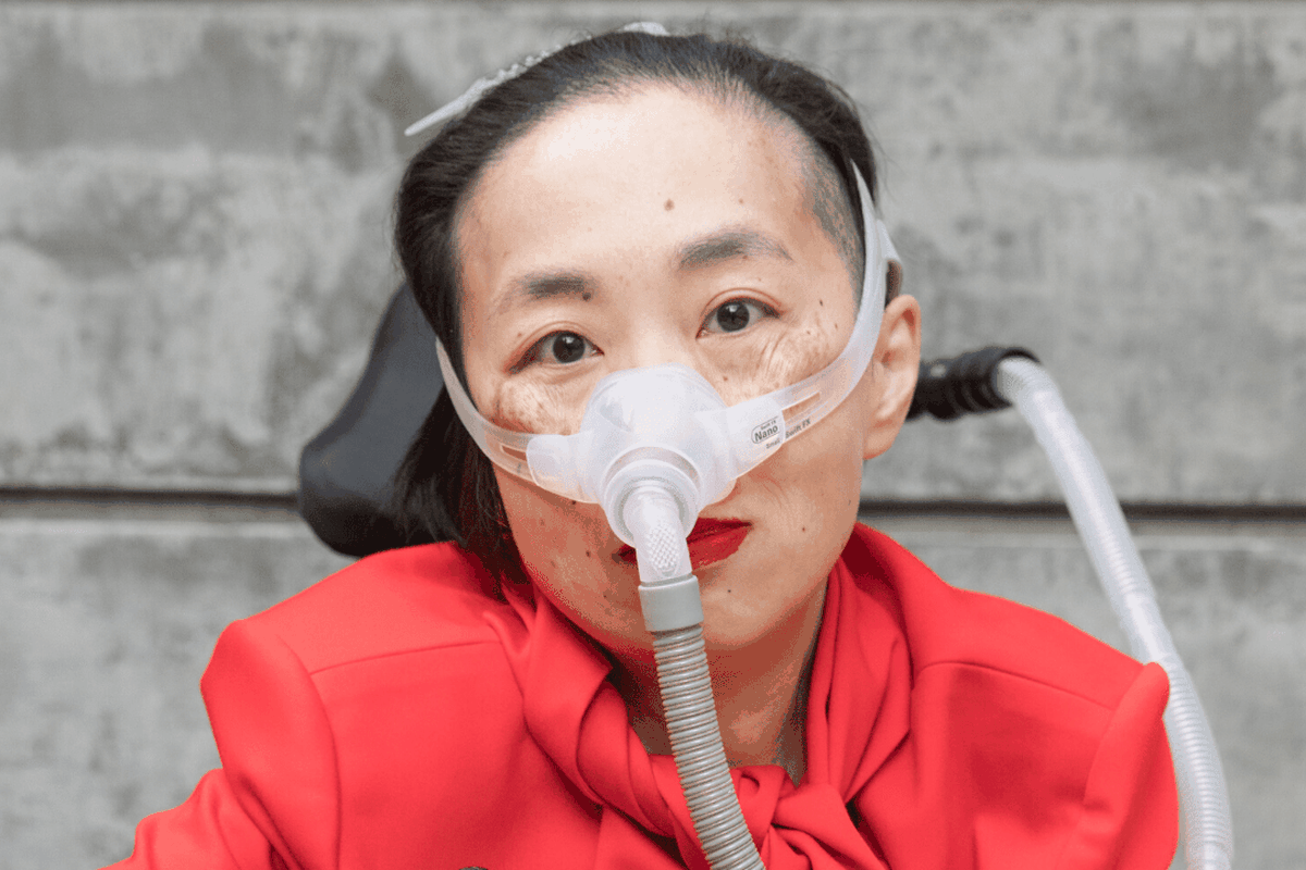 An Asian American woman, dressed in red, with a wheelchair, ventilator and facial oxygen tube.