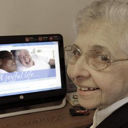 In this April 10, 2012, photo, sister Elaine Lachance works at a computer displaying a photo from the St. Joseph convent on it, in Biddeford, Maine. Good Shepherd Sisters of Quebec has just six convents in Maine and Massachusetts with fewer than 60 sisters. The youngest is 64, and it's been more than 20 years since a new member has joined. Sister Lachance is using the Internet, social media and even a blog to attract women who feel the calling to serve God.