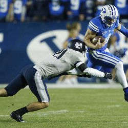 Brigham Young Cougars quarterback Taysom Hill (4) is tackled by Utah State Aggies safety Brian Suite (21) in Provo Friday, Oct. 3, 2014.