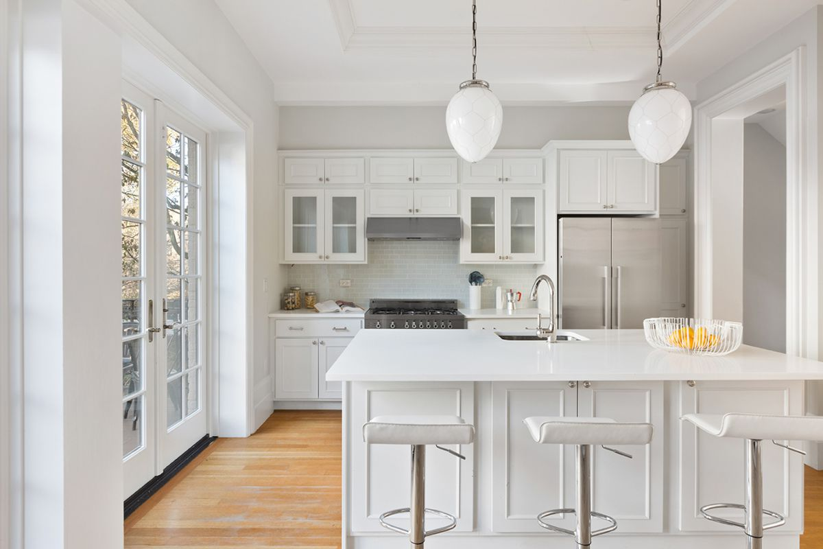 A kitchen with French doors that lead to an outdoor space, an island, and white cabinetry.