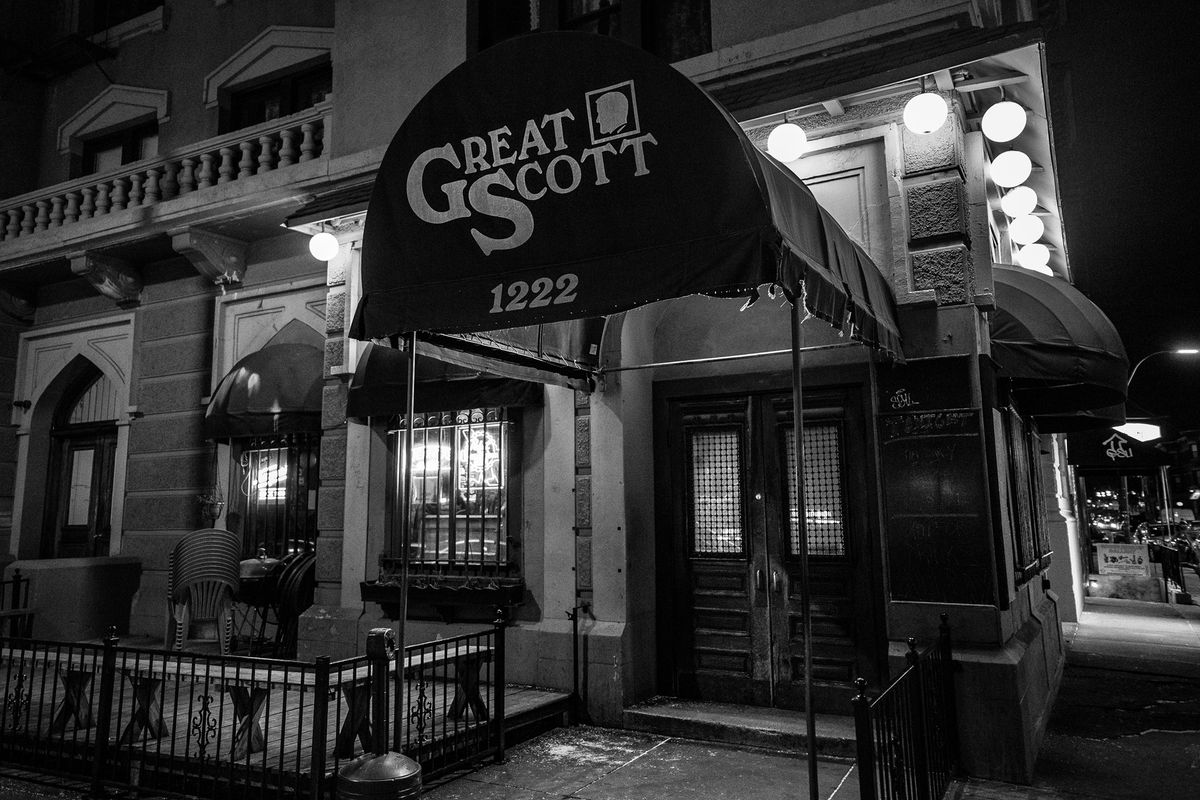 Exterior of a bar, with the name Great Scott written on the awning. The photo is black and white.