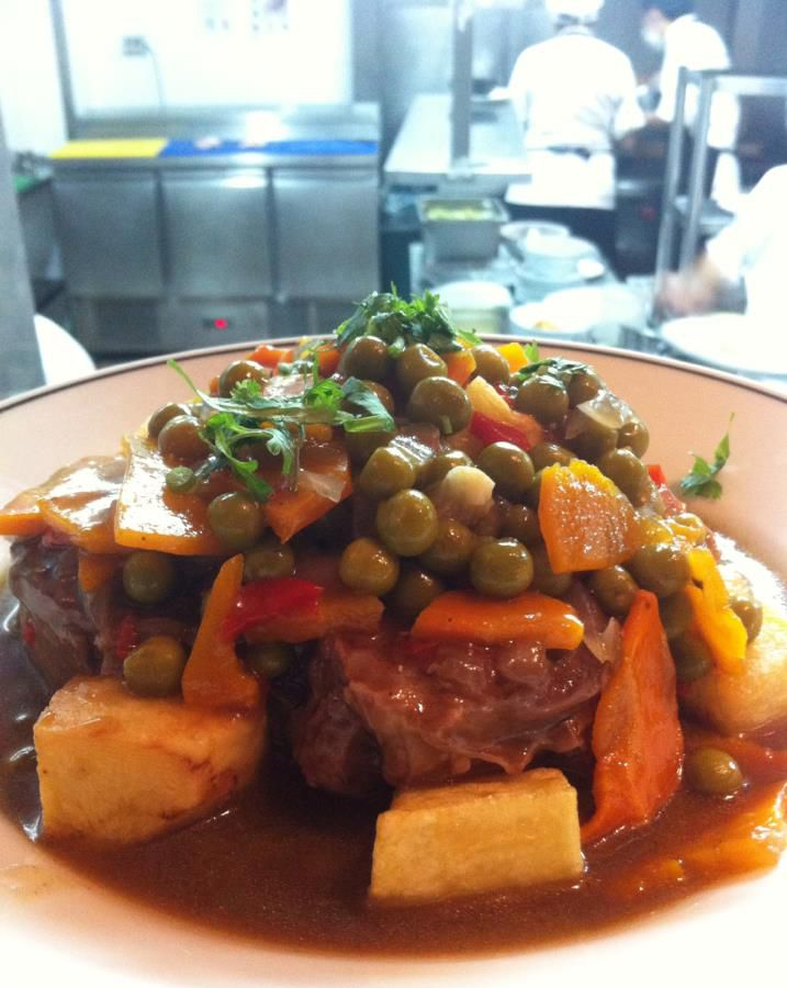 A close-up on a plate of steak topped with peas, carrots and other roasted vegetables in a thick sauce that pools in the plate