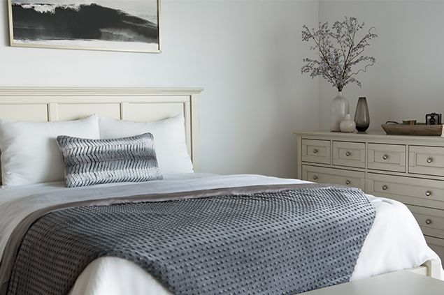 Bed with white bedding and gray blanket.