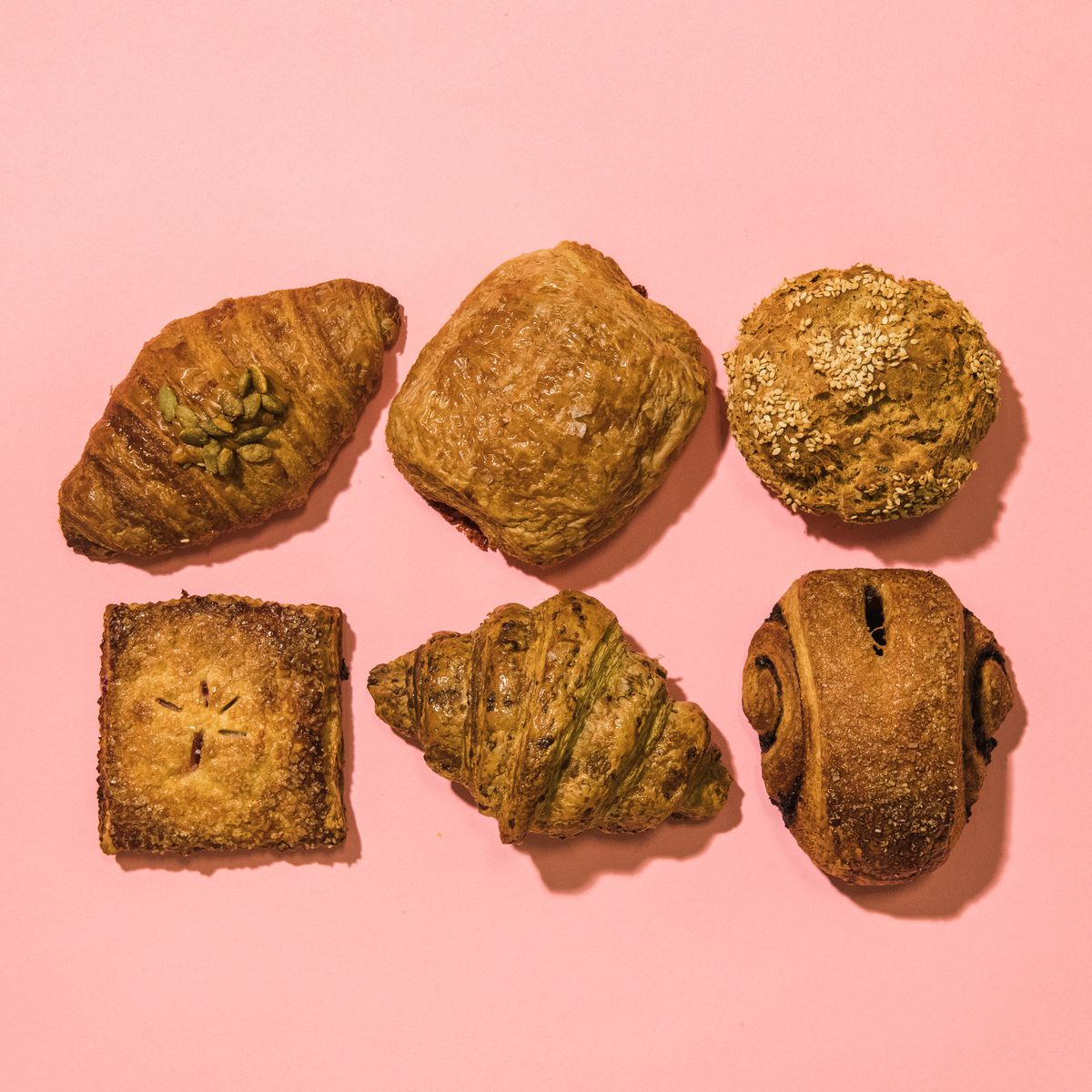 Six breakfast pastries laid out in two rows of three on a pink background