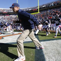 In this Oct. 22, 2016, file photo, Virginia coach Bronco Mendenhall leads his team onto the field for an NCAA college football game against North Carolina in Charlottesville, Va.