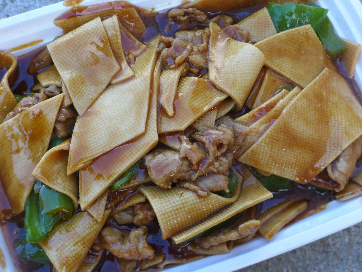 Wide brown noodles with a grid texture with gnarled pieces of pork and fresh green chiles in gravy.