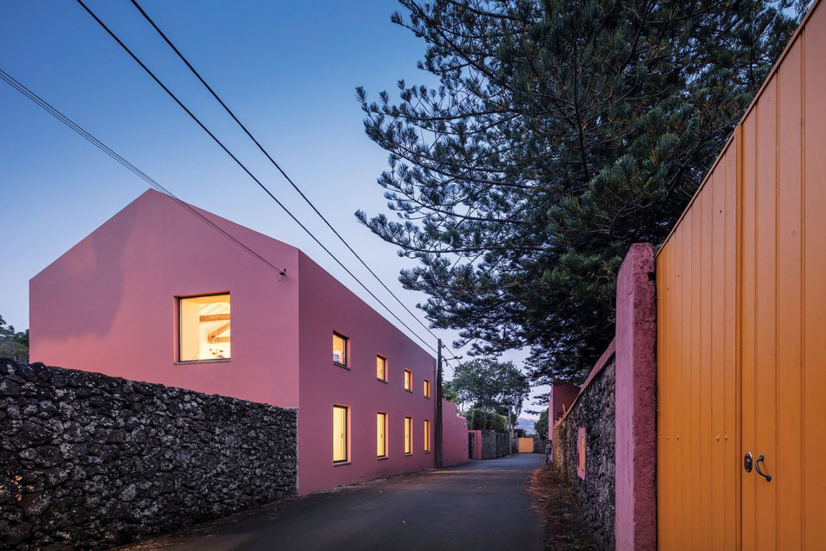 Simple gabled structure with pink exterior walls and a low stone containing wall.