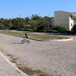 A Syrian boy rides a donated bicycle through the deserted streets of the Kyllini refugee camp in Myrsini, Greece, July 11, 2016. The camp was previously a luxury resort before it fell into disrepair and was later turned into a refugee camp.