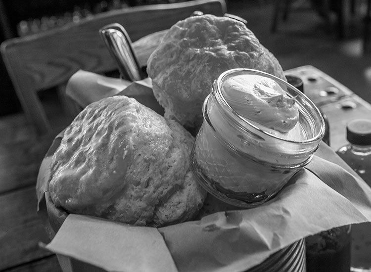 A dramatic black and white photo of a basket of large biscuits, accompanied by a small mason jar of butter
