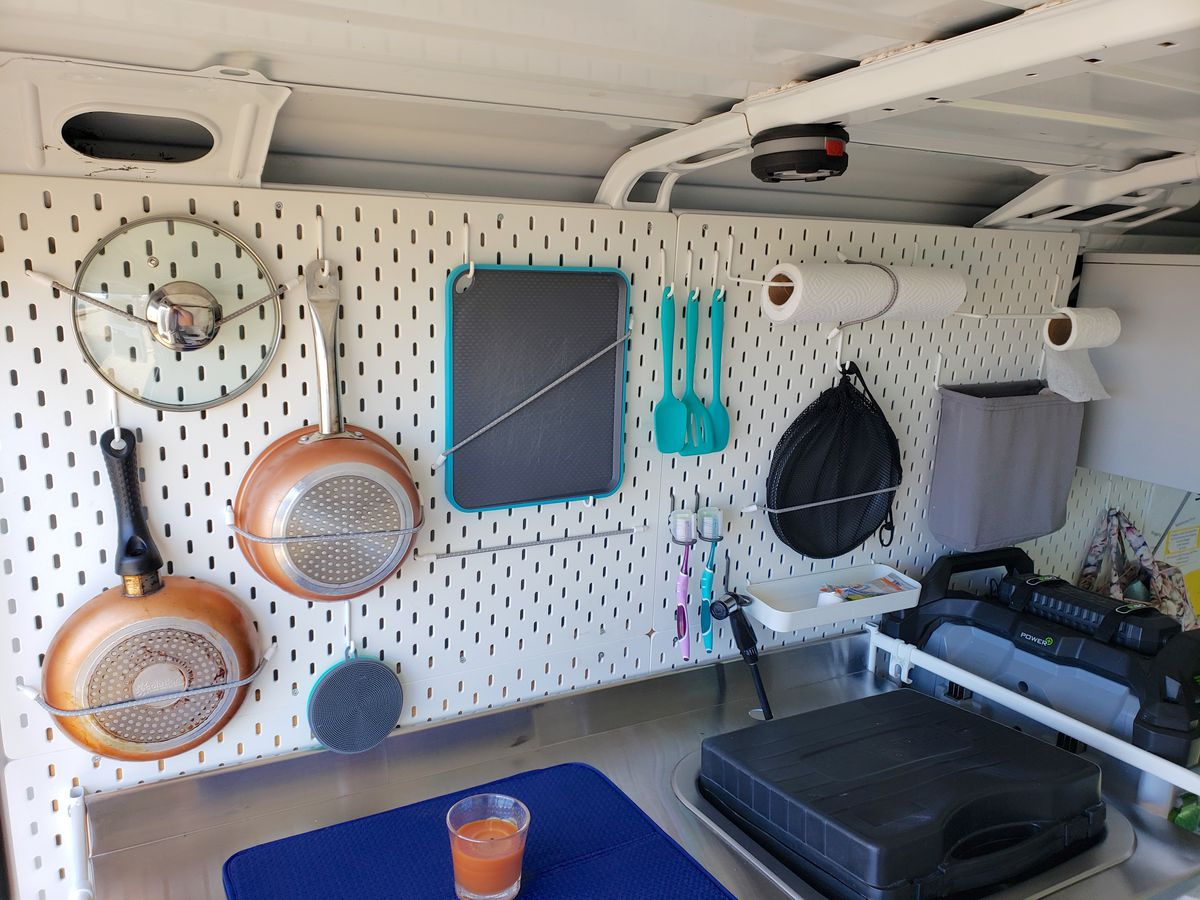 A white peg board has cooking supplies hanging on it, tied down inside a camper van.