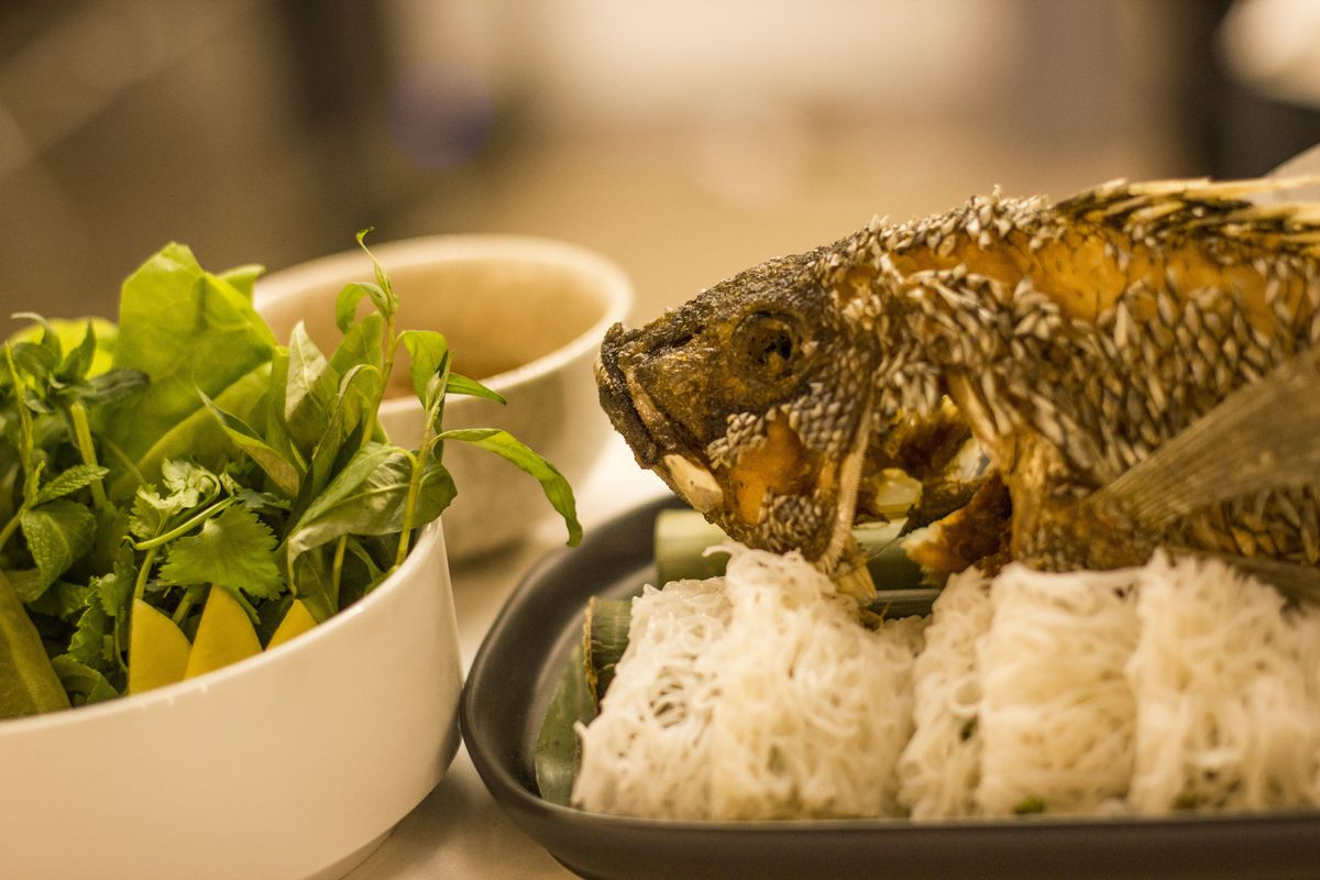A tray with noodles and a whole fried fish placed on top of it. Next to it is a white bowl filled with green herbs.