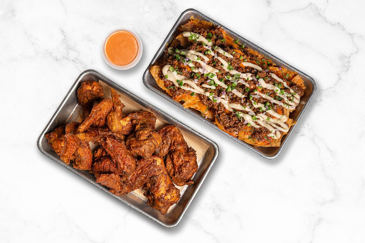 A tray of chicken wings next to a tray of nachos