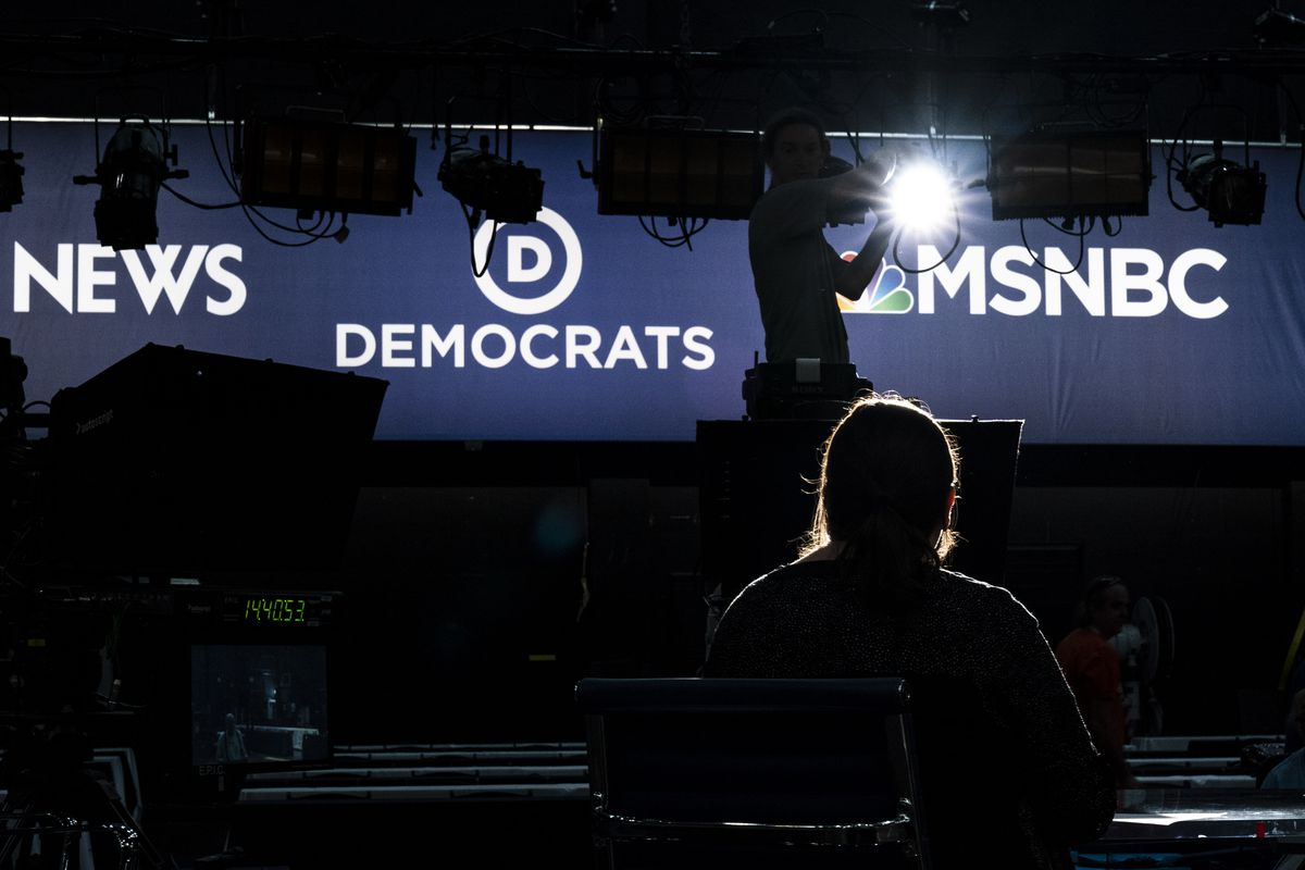"""The set for the first 2020 presidential primary debate with the words """"News"""" and """"Democrats"""" and """"MSNBC"""" on the backdrop."""