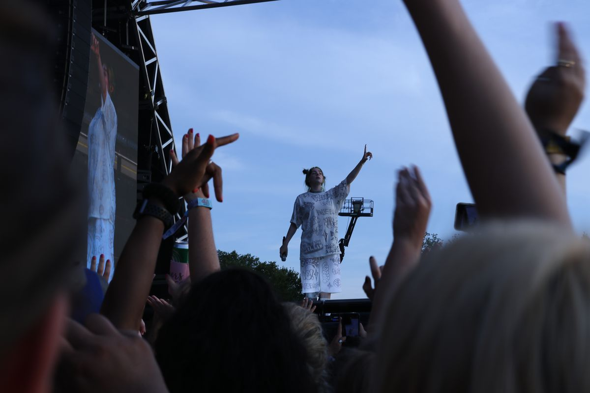 Seventeen-year-old Billie Eilish takes the stage, wearing baggy white clothes adorned with her stage name.