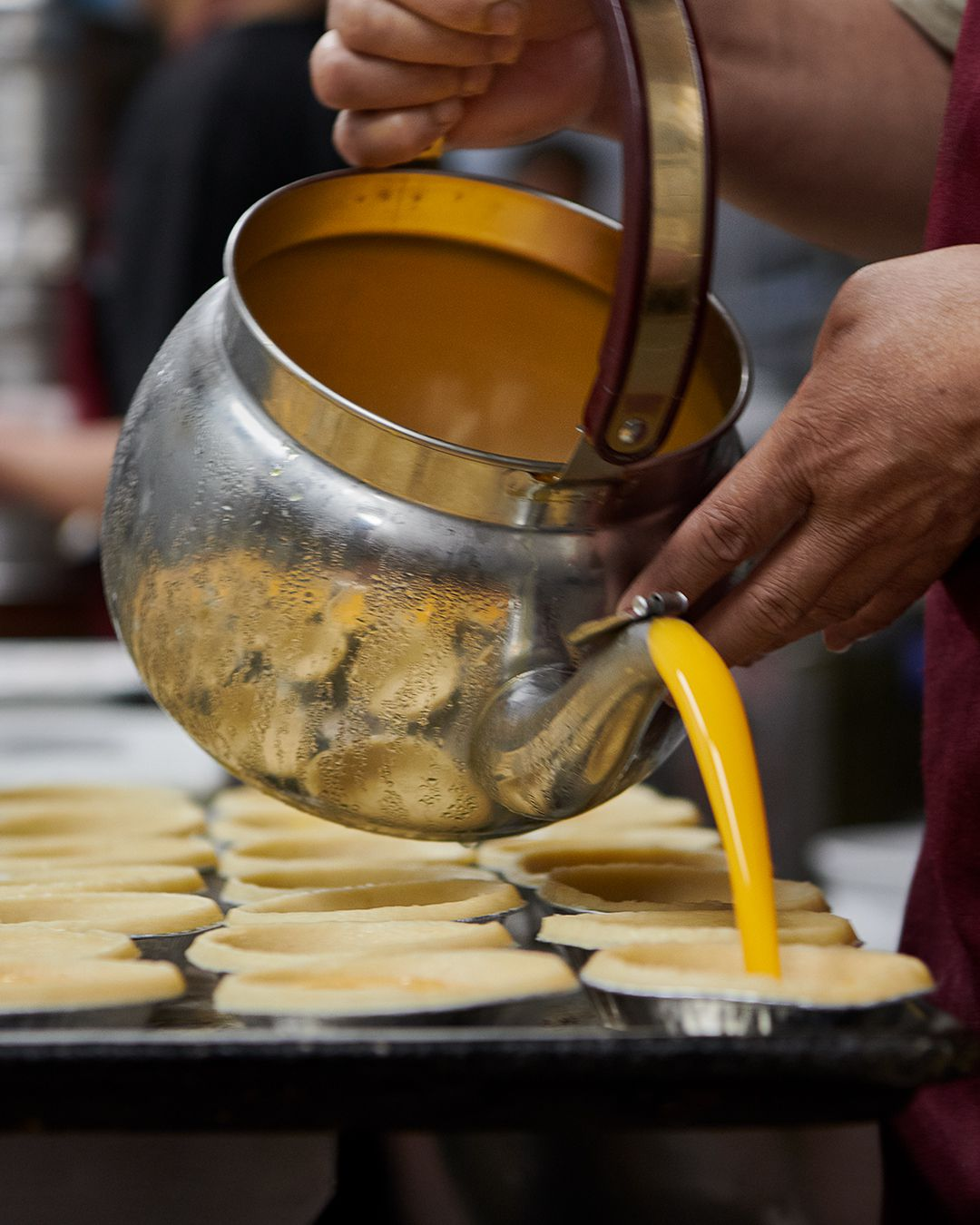A pitcher pouring egg mixture into tarts.