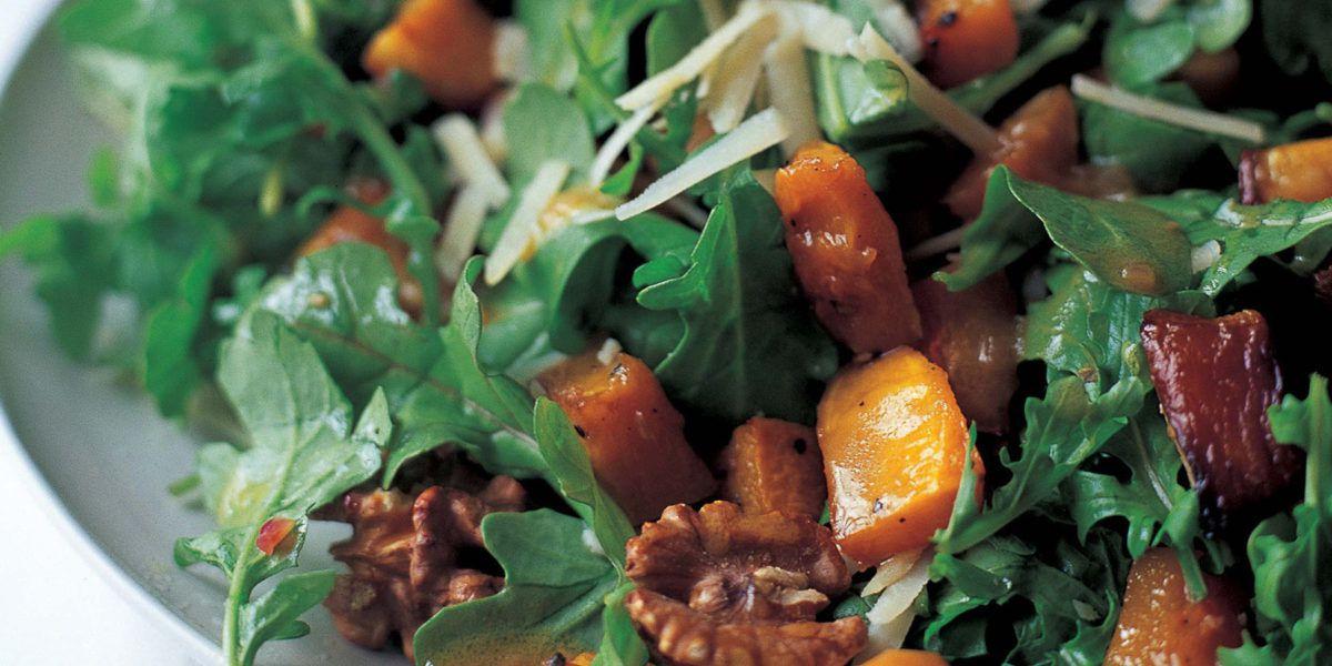 A close-up of a salad with squash, walnuts, arugula, and parmesan cheese