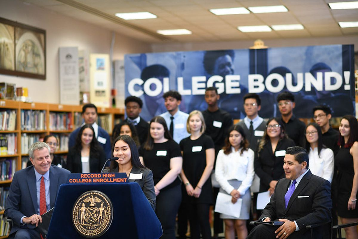At a press conference about college enrollment, Mayor Bill de Blasio and Chancellor Richard Carranza listen to an alum of High School of Telecommunication Arts and Technology talk about her experience enrolling in college.