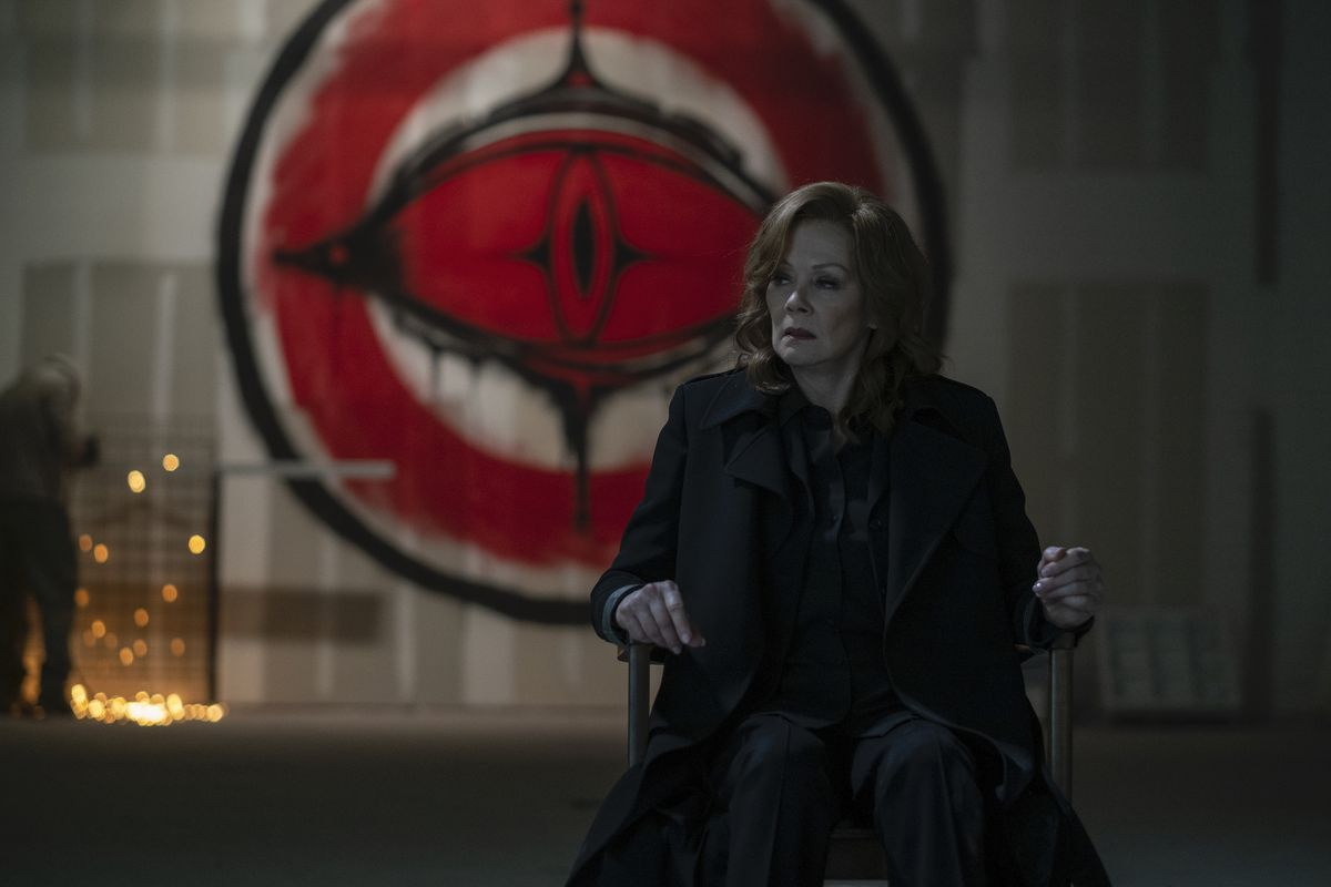 Laurie (Jean Smart) sits handcuffed to a chair in front of the Cyclops logo