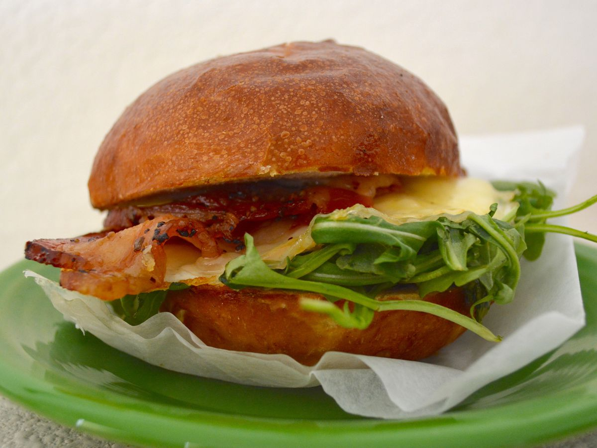 A breakfast sandwich stuffed with egg, bacon, and arugula on a green plate