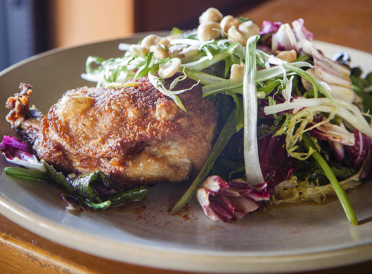 A plate of greens with a crispy duck leg.