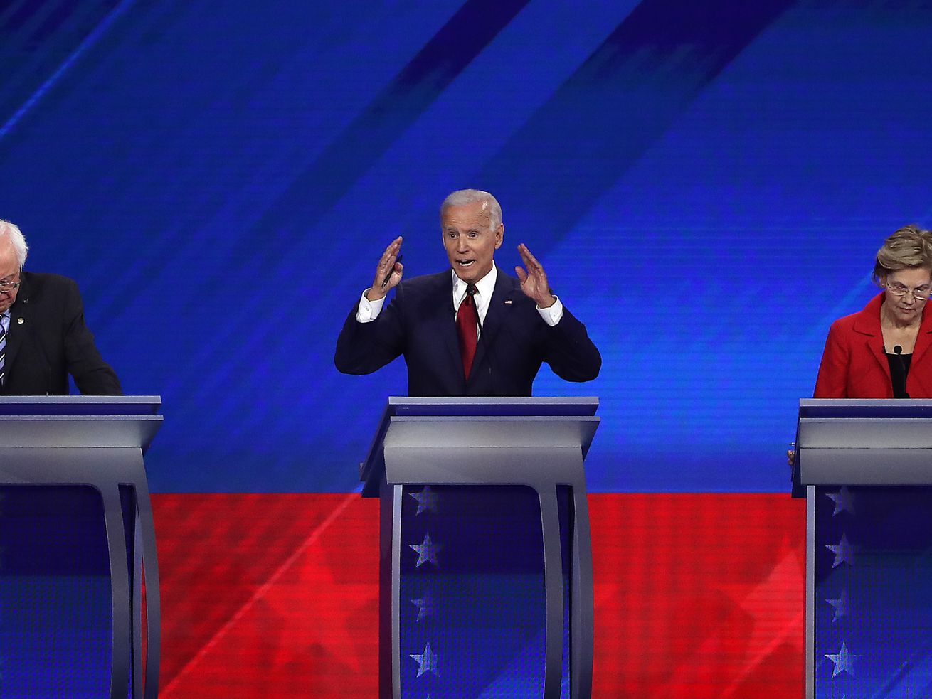 Joe Biden, at the center podium, speaks with his hands up at the Democratic debate on September 12, 2019, while Senator Bernie Sanders to his right and Senator Elizabeth Warren to his left look down at their podiums.
