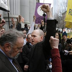 Tim DeChristopher raises his fist along with those who have gathered to support him as he leaves court following a guilty verdict on two federal charges in Salt Lake City on Thursday, March 3, 2011.