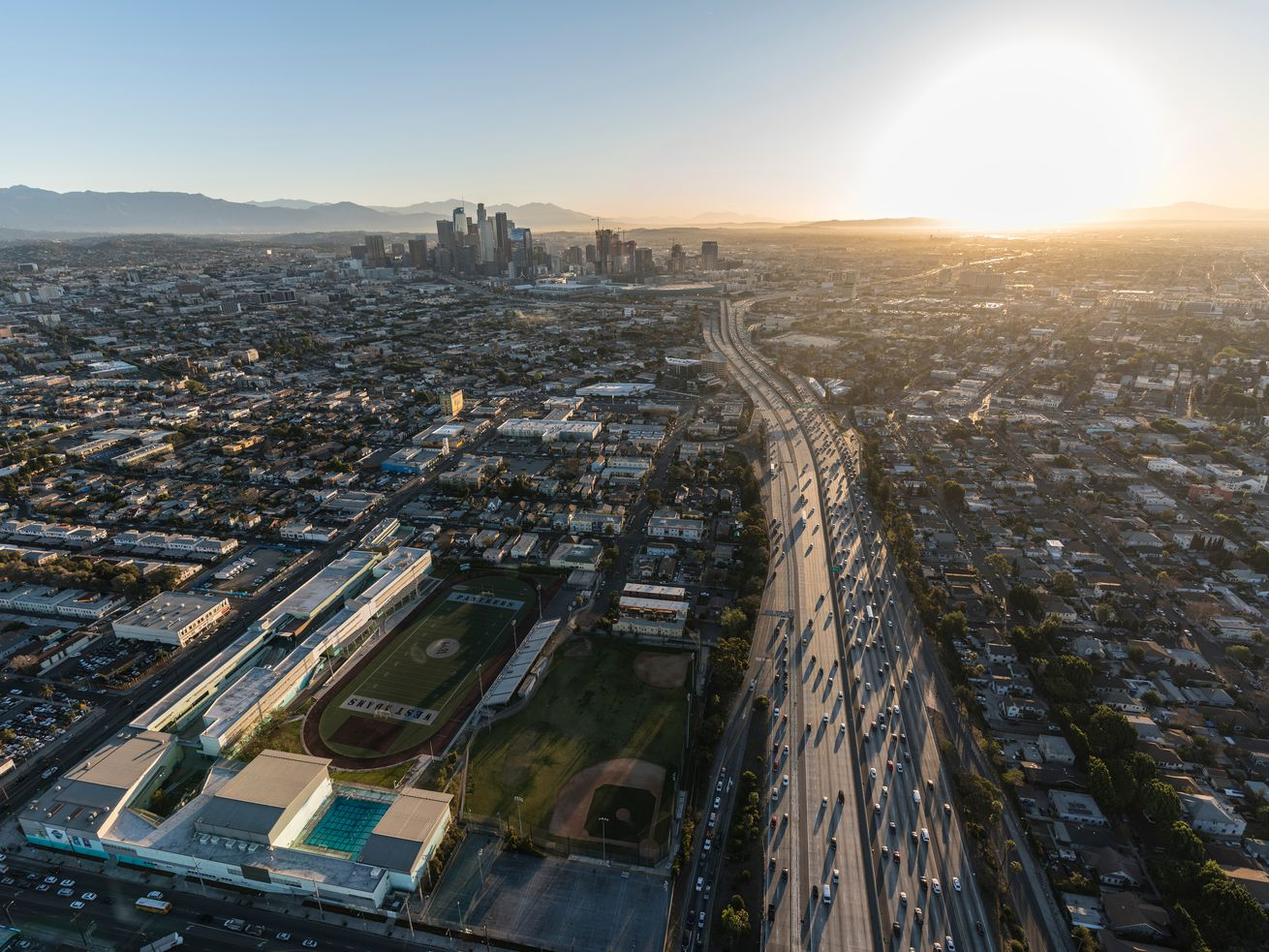 Aerial view of a Los Angeles freeway with the Downtown skyline in the distance