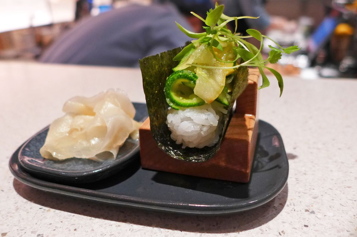A u shaped sushi roll is cradled in nori and contains green summer squash, scallions, and micro