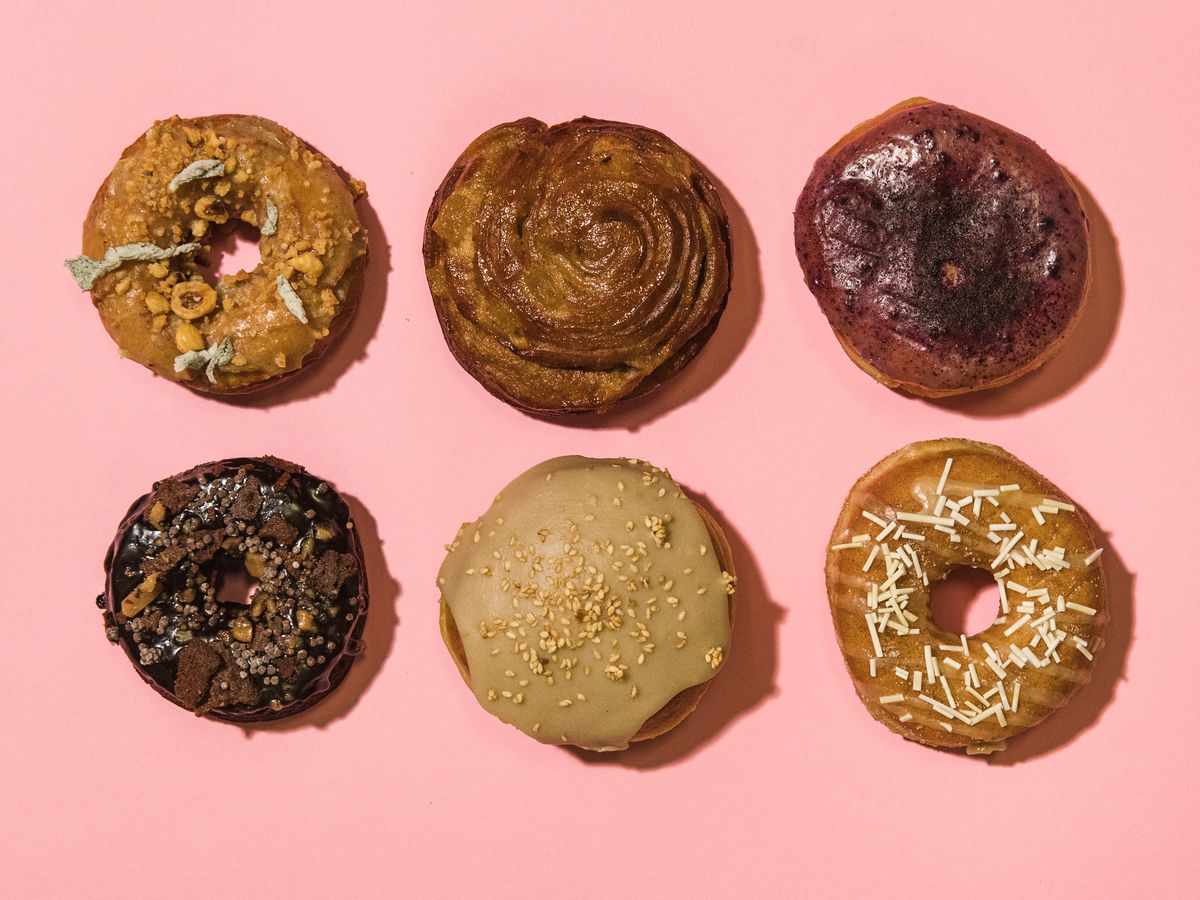 Six doughnuts are laid out in two rows of three on a pink background