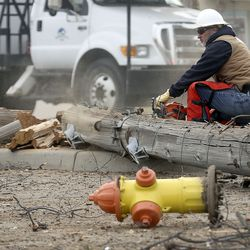 A utility worker saws through a downed power pole at the scene of a collision involving eight vehicles spanning the block between 300 East and 400 East on 400 North in Bountiful on Thursday, Dec. 10, 2020. A dump truck hit a power pole and seven vehicles, some vacant and parked, leaving four people injured.
