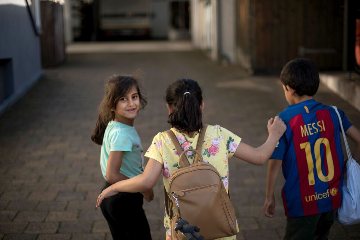 Three of the Al Hammoud's children (from left, Nada, 6; Nour, 10; and Mahmoud, 8) walk up the driveway of their home in Neu-Anspach, Germany. The Al Hammoud parents say the main reason they left their bombarded home in Syria was to ofter their children a safe and secure future.