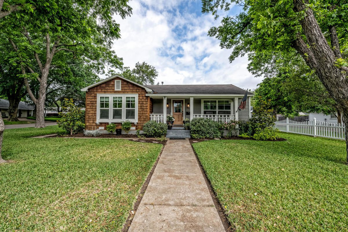 An exterior view of a small cottage, called the Baker House, in Waco, Texas, featured on Fixer Upper. There is a front porch, long sidewalk, and green grass.