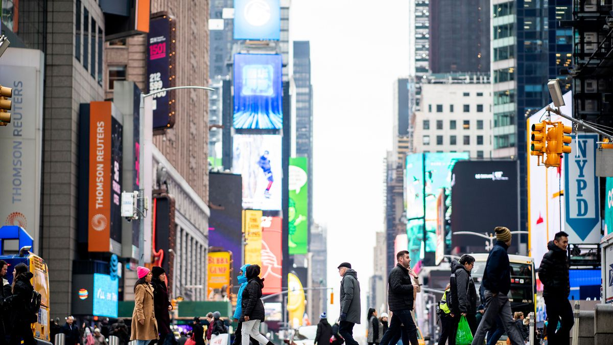 A crowd of people walking across 42nd Street in Times Square on January 14, 2020
