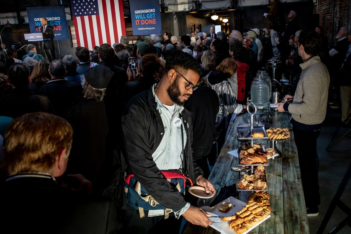 Bloomberg speaks as a voter grabs food from a table