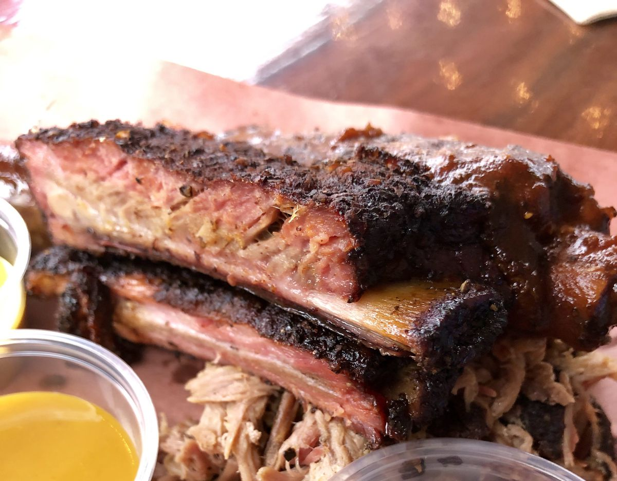 One wet rib and one dry rib at Bark City BBQ. On the Pitmaster Nap, ribs arrive on top of a pile of pulled pork.