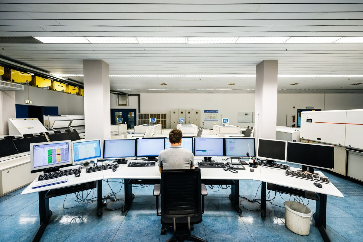 Back shot of an engineer sitting on a desk and working on computers in a large clean control room of a modern printery
