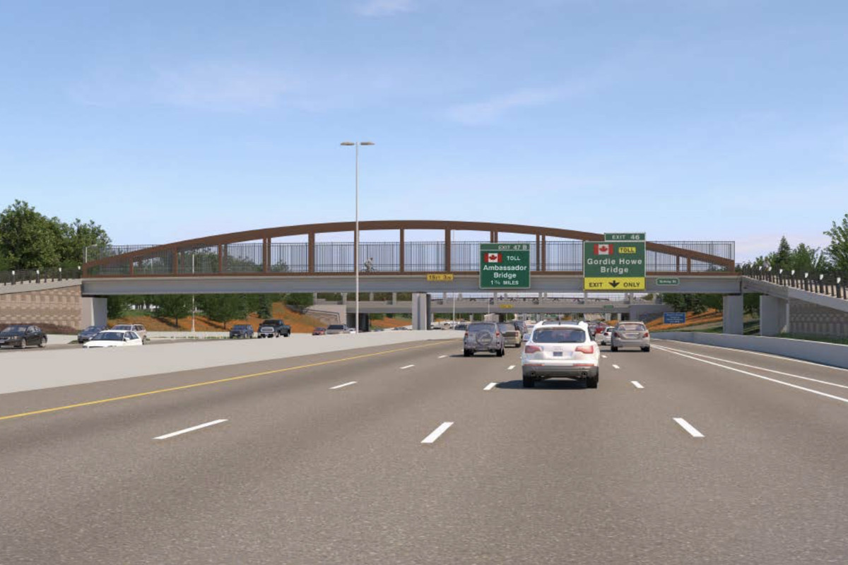 Driver's view on a four-lane freeway. In the near distance, there's a pedestrian bridge with a red metal framing.
