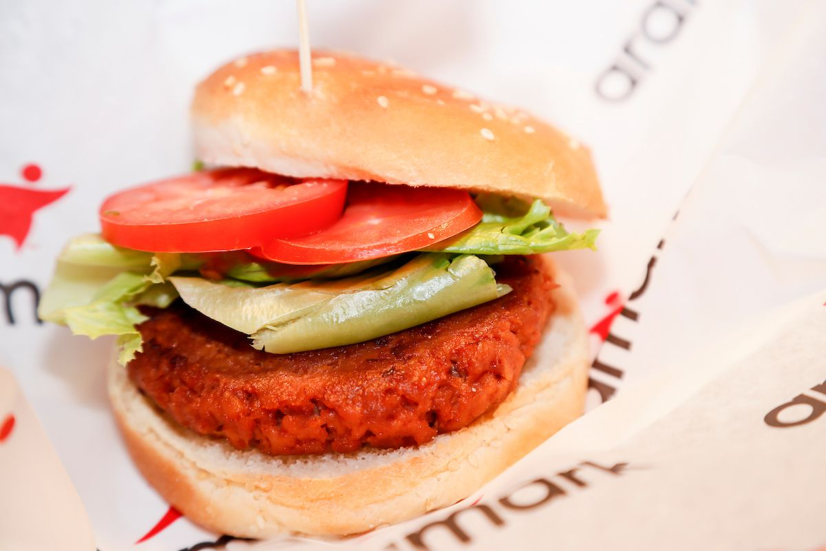 A veggie burger with lettuce and tomato on a bun.