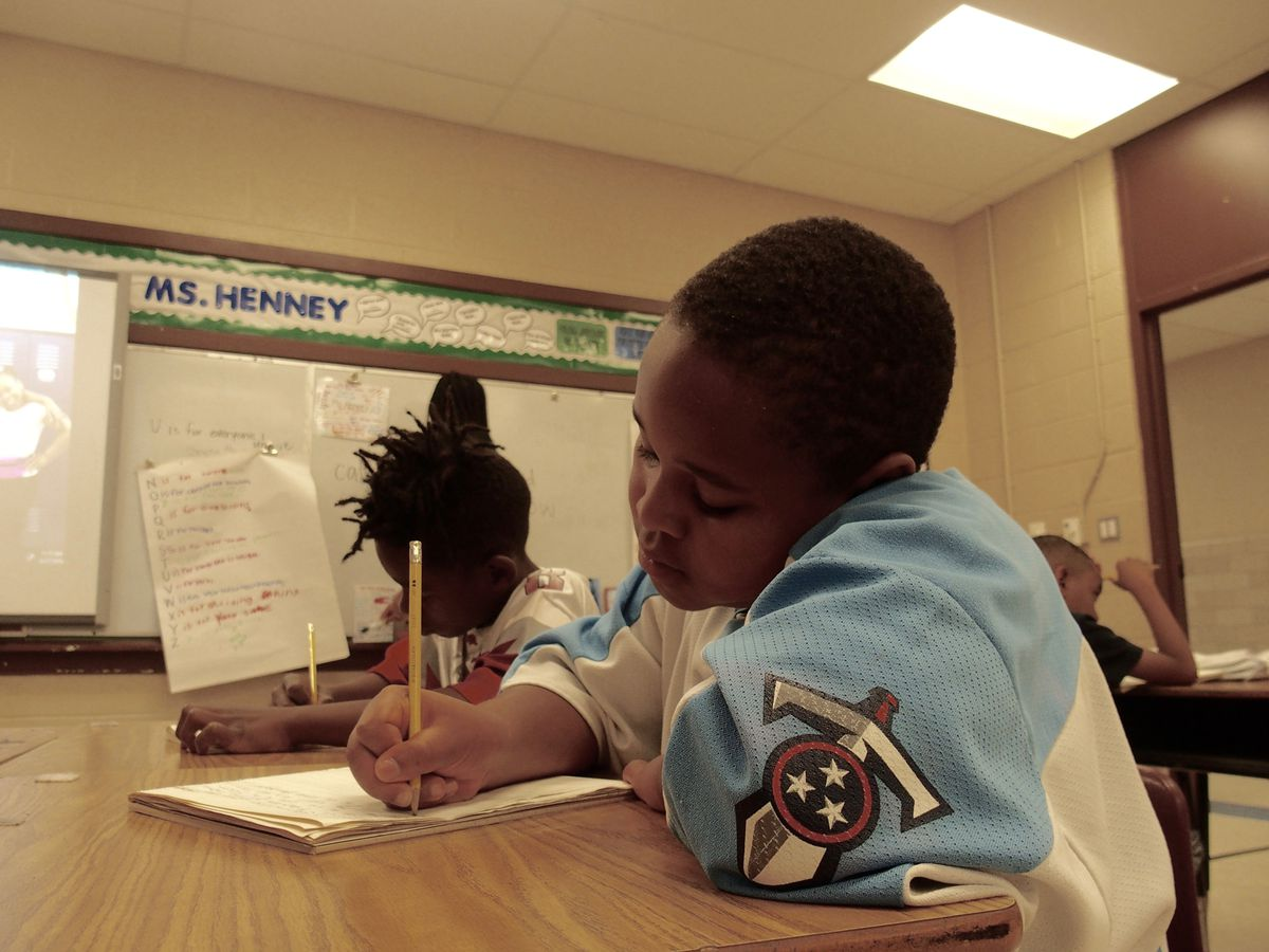 Third-grader Brieston Fleming, 8, writes a story about his favorite athlete, Dwayne Johnson, after reading several books about sports stars during the last week of the state-funded Read to be Ready literacy camp at Cornerstone Prep in Memphis' Frayser neighborhood. June 27, 2019.