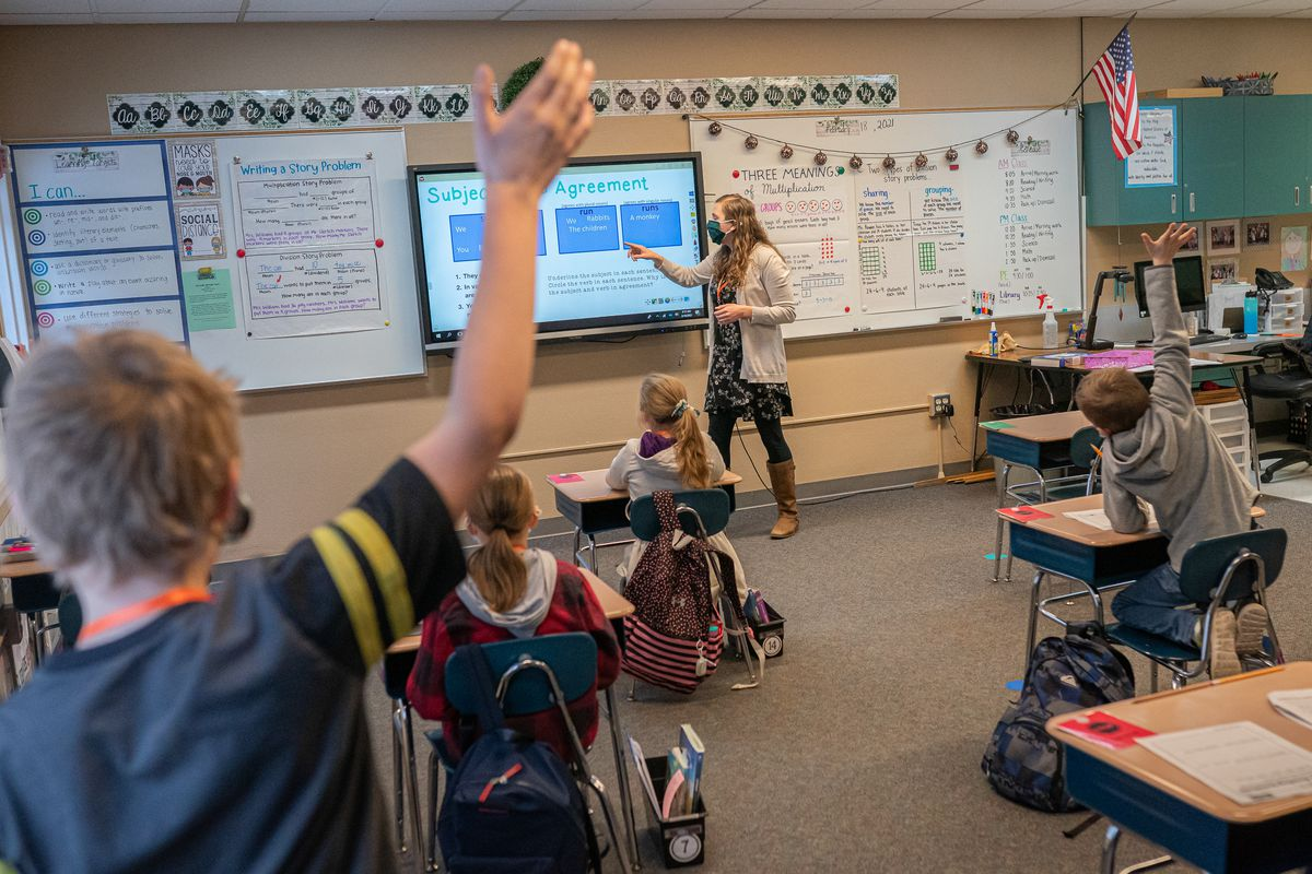 A young student raises his hand in the foreground as his classmates listen to their teacher at their desks. The teacher is pointing at a smartboard at the front of the classroom.