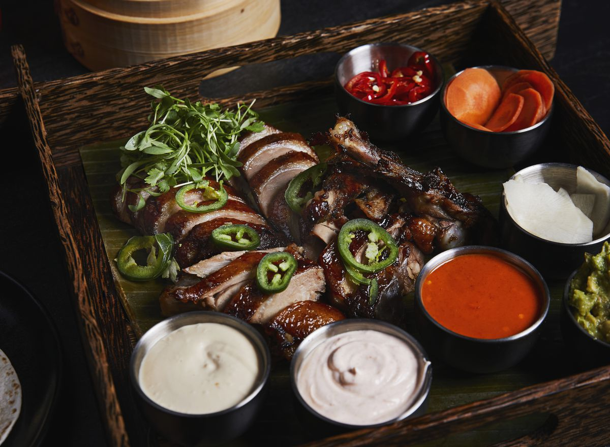 sliced duck on a wooden plate topped with greens and surrounded by sauces