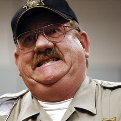 Utah County sheriff's deputy Cameron Baxter grimaces as he experiences a shock from a Taser.