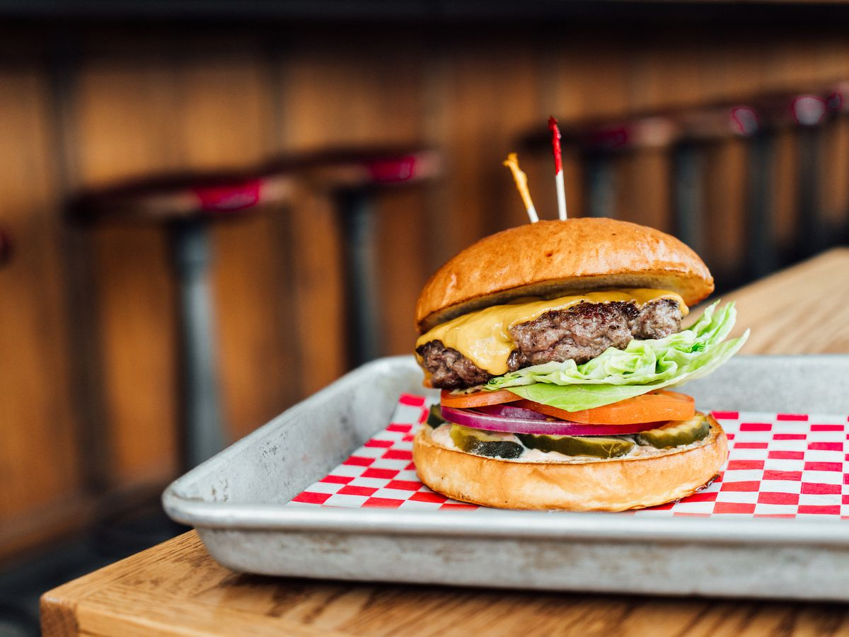 A classic burger with lettuce on a red checkered paper tray.