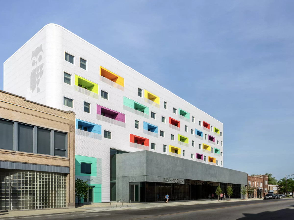 An exterior angle of a five-story library building with a gray lower level and a corrugated upper mass with multicolored inset balconies.