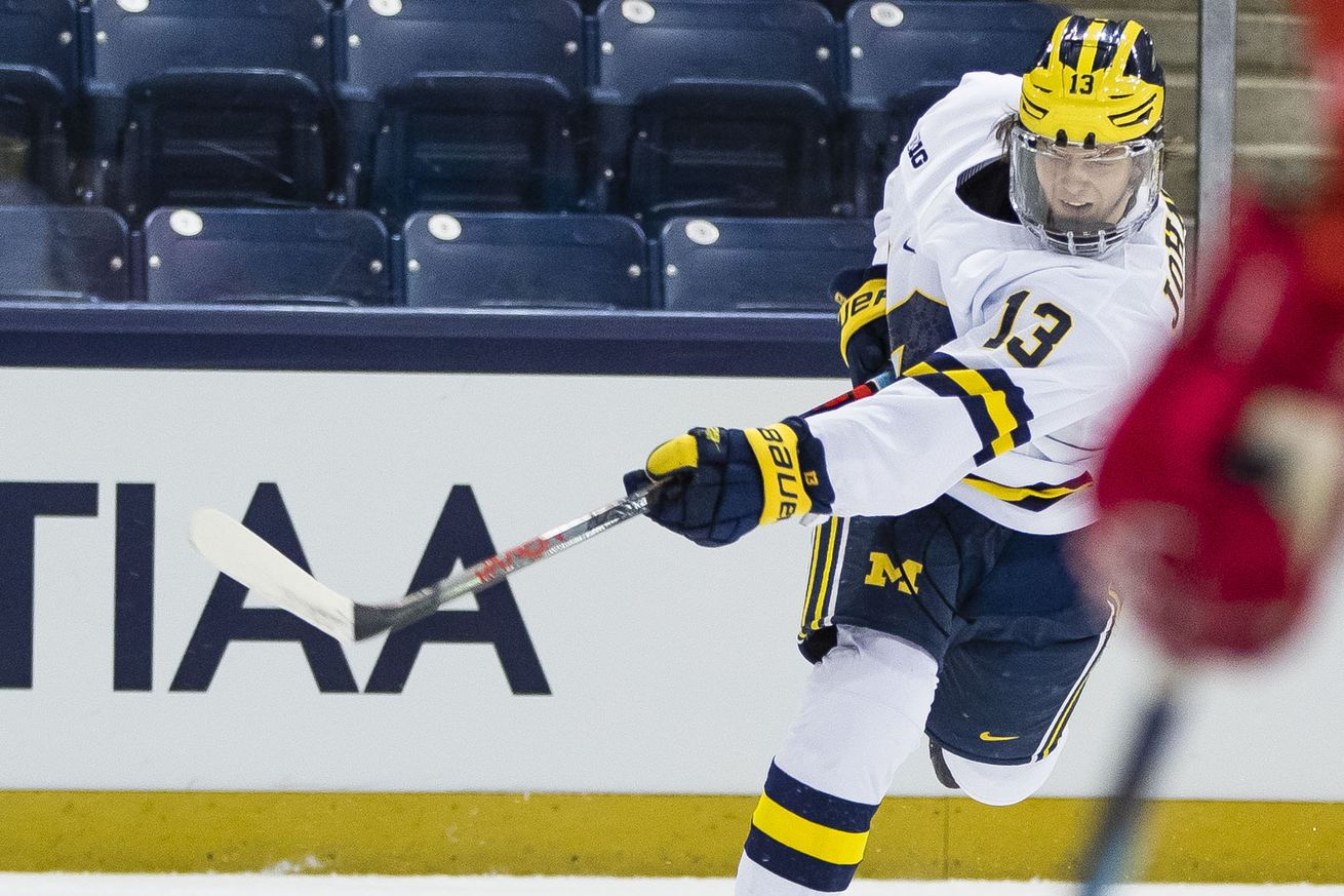 Michigan's Kent Johnson (13) shoots during the Michigan vs. Ohio State Big Ten Hockey Tournament game Sunday, March 14, 2021 at the Compton Family Ice Arena in South Bend.