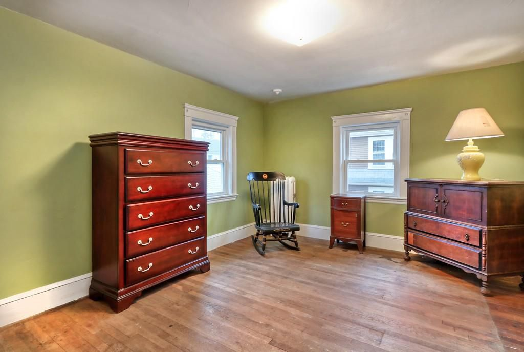 A bedroom with two dressers, two windows, and a rocking chair.