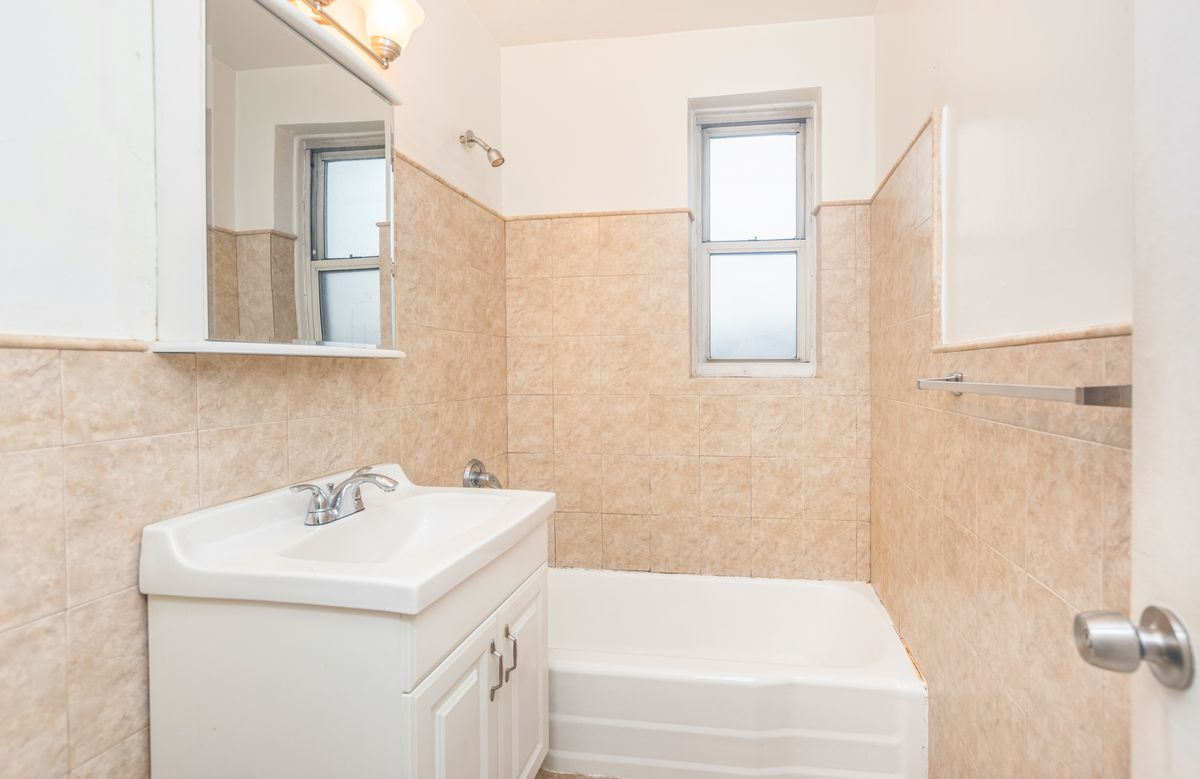 A small bathroom with beige tiles.